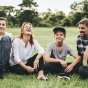 family-sitting-grass-laughing