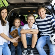 Joyful family of four sitting in the back of an SUV